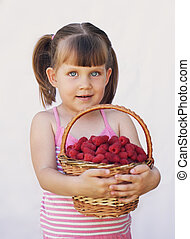 girl holding a basket of raspberries