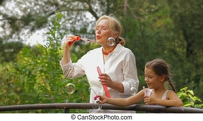 Family Blowing Bubbles - Grandmother and granddaughter...