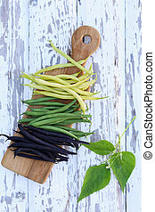 beans on a wooden board - pods of fresh long beans on a...