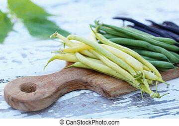 pods of beans on a board - pods of fresh long beans on a...