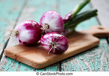 Fresh purple onion on a wooden board