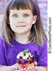 Little girl holding a pastry with blueberries