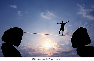 Man Balancing on the Rope - Highline walker in blue sky...