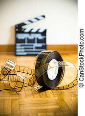 Cinema film reel and out of focus movie clapper board - 35...