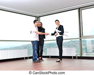 happy young couple buying new home with real estate agent...