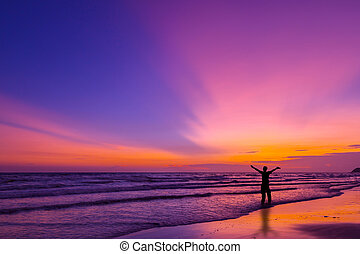 Silhouette of a man on the beach at twilight