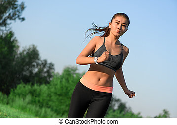 Sporty young asian woman jogging at park