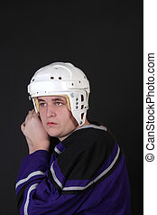 Teen male hockey player putting on safety helmet, getting...