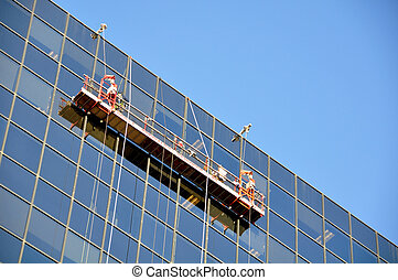 Window Washer - Two window cleaners in a gondola cleaning...