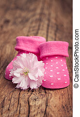 Baby girl shoes with pink flower on vintage wood