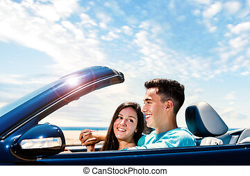 Happy couple driving convertible along seaside. - Close up...