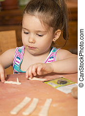 Little girl playing with dough - Happy little chef smeary...