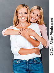 Family bonds Smiling young woman embracing her mother while...