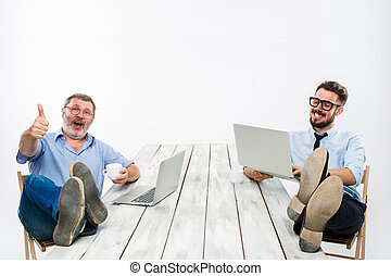 The two businessmen with legs over table working on laptops...