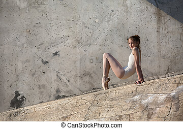 Slim dancer sits in a ballet pose leaning on her hands on a...