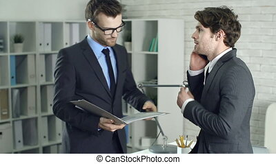 Interrupted Discussion - Two businessmen talking in office...