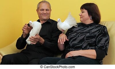 Mature Couple And Pigeons - Mature couple sitting on a couch...