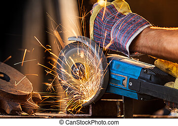 Close-up of worker cutting metal with grinder. Sparks while...
