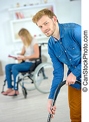Vacuuming  for his disabled girlfriend