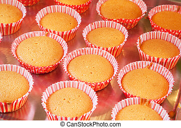 Baking cup cakes - baked red cup cakes at the baking tray