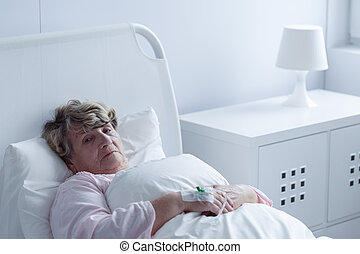 Sick older woman - Tired sick older woman lying in hospital...