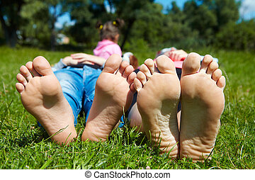 Family lying on the grass. Rest in the park