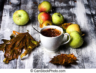 table tea apple and rain - Cup of tea standing on wooden...