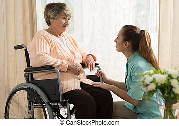 Caregiver helping old female - Picture of caregiver helping...