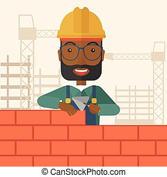 Black builder man is building a brick wall - A smiling black...