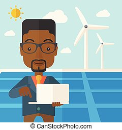 African man with laptop in solar panel - An african man with...