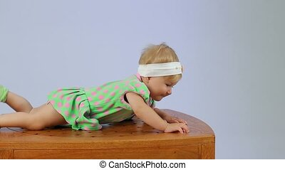 Child Lying On A Wooden Table - A small child lying on a...