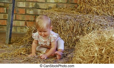 Cute Little Baby - A small child sitting on a haystack.