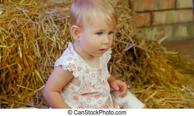 Girl Sits On A Farm - A small child sitting on a haystack.