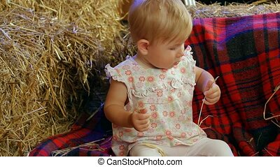 Farm Kid In A Haystack - A little girl sits in a haystack...
