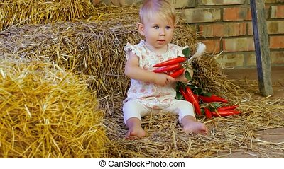 Child With A Toy - A small child sitting on a haystack.