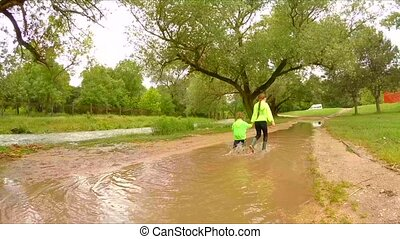 Two Children Walking In Puddles In Park - This rear shot was...