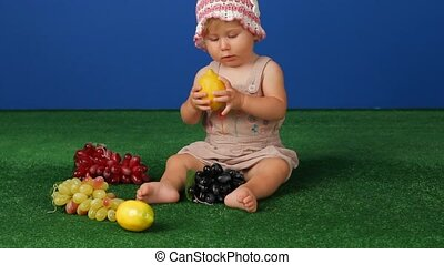 Pick Up A Lemon - Little girl sitting on green grass next to...