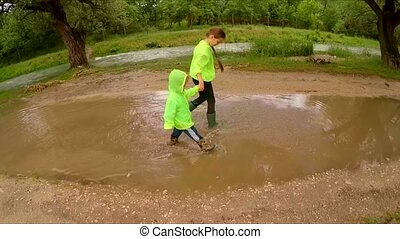 Happy Children Walking In Puddles In Park