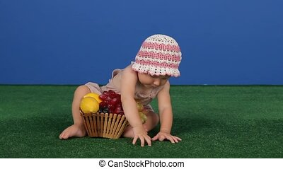Child Next To A Basket Of Juicy Fruits - The child sits on...