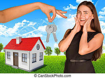 Happy young lady with house and hand holding keys