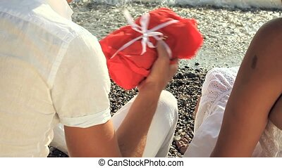 Man and Woman Open A Red Bundle Sitting on the Beach - Shot...
