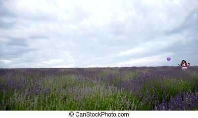 The girl runs with a purple ball in a field of lavender -...