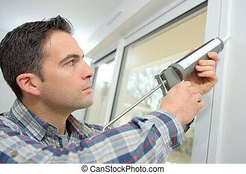 Handyman caulking a window