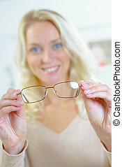 Lady holding spectacles, closeup