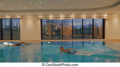 People Swimming in the Pool - Man and woman are swimming in...