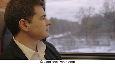 Thoughtful Man in Train - Young man in business suit is...