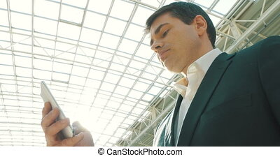 Businessman with Smartphone in Modern Building - Low-angle...