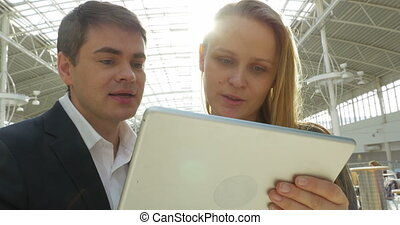 Friends Using Tablet PC in Public Place - Male and female...