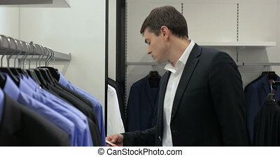Man in Menswear Store - Young man in suit is looking price...
