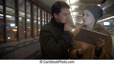 Couple Planning Their Evening with Tablet PC - Young couple...